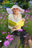 Elegant elderly lady reading in the garden — Stock Photo