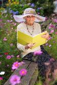 Modne staruszka czytanie w swoim ogrodzie — Zdjęcie stockowe