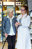 Pharmacist gently holding and supporting senior female patient — Stock Photo