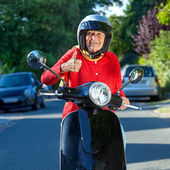Cheerful senior woman on a scooter — Stock Photo