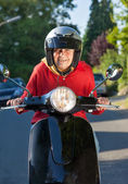 Laughing senior woman riding a scooter — Stock Photo