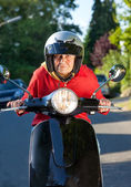 Senior woman riding a scooter crouching low over the handlebars — Stock Photo