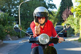 Old lady on a scooter making a rude gesture — Stock Photo