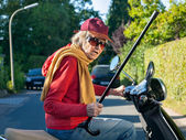 Senior lady riding on a scooter waving her cane — Stock Photo