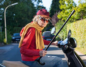 Bad tempered old woman on a scooter — Stock Photo