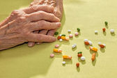 Clasped hands of an elderly lady alongside medication — ストック写真