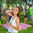 Young girl with her friends in the park — Stock Photo