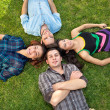 Two teenage couples relaxing on the grass. — Stock Photo