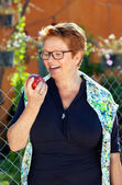 Senior woman laughing as she holds a red apple.  — Stock fotografie