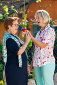 Laughing senior woman giving her friend an apple.  — Stock Photo