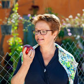Healthy senior woman eating a red apple.  — Photo
