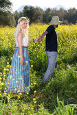 Woman being led through flowers field — Stock Photo