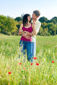 Couple embracing in a poppy field — Stock Photo