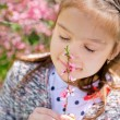 Little girl snuff flowers — Stock Photo