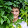 Cheerful happy boy peeking out from behind the leaves of trees — Stock Photo #32470587