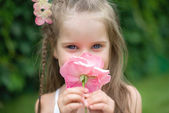 Little cute girl in garden snuff flower — Stock Photo