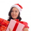 Young happy girl in Christmas Santa hat holding christmas gift — Stock Photo #35467713