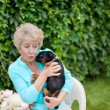 Attractive senior woman playing with her puppy in the backyard — Stock Photo