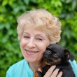 Beautiful smiling senior woman with small dog in the summer park — Stock Photo #39980799