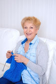 Happy smiling senior woman knitting on her sofa at home — Stock Photo