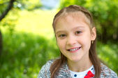 Outdoor portrait of a cute young little girl in the park — Stok fotoğraf