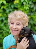 Hermosa mujer sonriente senior con pequeño perro en el parque de verano — Foto de Stock