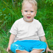 Cross-legged little boy sitting on the grass  — Stock Photo