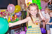 Cute smiling girl holding balloon on a birthday party — Stock Photo