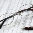 Stock Photo: Eyeglasses and pencil on document