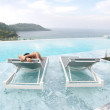 Tourist sleep on deckchair and swimming pool  — Foto de Stock