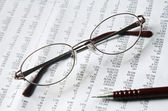 Eyeglasses and pencil on document — Stock Photo