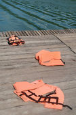 Life vest on wood floor with a boat on river background — Stock Photo