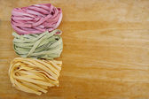 Colorful pasta fettuccine and wood — Stock Photo