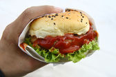 Hand hold hamburger on white — Stock Photo