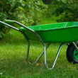 Green wheelbarrow in green garden — Stock Photo #29471273