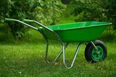 Green wheelbarrow in green garden — Stock Photo
