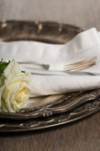 Silver plate, fork and knife setting with white rose on wooden t — Stock Photo