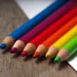 Rainbow coloring pencils on wooden table on top of empty white — Stock Photo