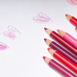 Stock Photo: Red and pink coloring pencils on top of white paper with naive