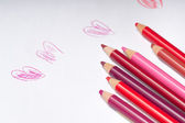 Red and pink coloring pencils on top of white paper with naive — Stock Photo