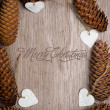 Merry Christmas carved on wooden table surrounded by decoration. — Stock Photo