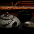 Stock Photo: Japanese iron teapot and heap of teleaves before mahogany back