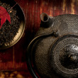 Japanese iron teapot and heap of tea leaves from top. — Stock Photo