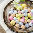 Colorful easter eggs on plate and blooming apple tree branch — Stock Photo