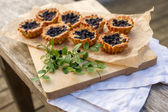 Eight small homemade blueberry pies on wooden table. — Stock Photo