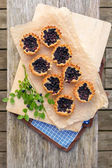 Eight small homemade blueberry pies on wooden table from top. — Stock Photo