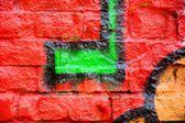 Pared de ladrillo antiguo con colorido graffiti — Foto de Stock