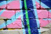 Gammal tegelvägg med färgglad graffiti — Stockfoto