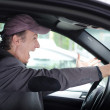 Angry upset man at wheel driving his car screaming — Stock Photo