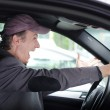 Angry upset man at wheel driving his car screaming — Stock Photo #28276023
